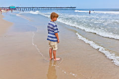 Boy walking on the beach Stock Image