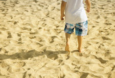 Boy walking on the beach in sunset Stock Image
