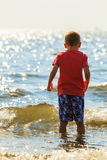 Boy walking on beach. Stock Image