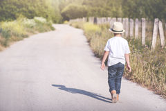 Boy walking. Child walking on a road Royalty Free Stock Photography