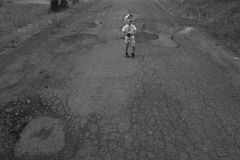 Boy walking on the cracked road Stock Image