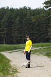 Boy walking with a dog near the forest Stock Photo