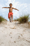 Boy walking down dune Royalty Free Stock Images