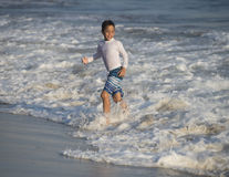 Boy walking in the edge of the ocean Royalty Free Stock Image