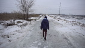 Boy walking on frozen road stock video footage