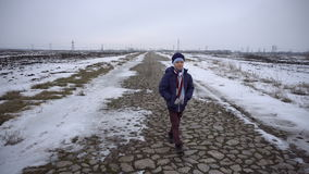 Boy walking on frozen road. The boy is in the winter on frozen road. Shooting with Steadicam 4K stock video