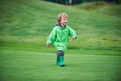 Boy walking the golf course. Little boy walking the green golf course Royalty Free Stock Photography