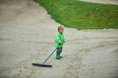 Boy walking the golf course. With a rake Royalty Free Stock Photography