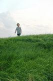 Boy Walking on Hill. Young boy hiking along a grass covered dike at sunset Royalty Free Stock Images