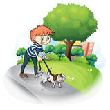 A boy walking with his dog along the street Royalty Free Stock Photo