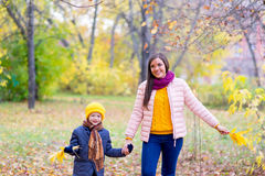 Boy walking with his mother in autumn park Royalty Free Stock Image