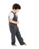 Boy walking imaginary line. Little boy in a suit and bare feet walking an imaginary line against a white background Stock Images