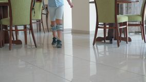 Kid undergoing treatment with electrical stimulation. Boy walking indoor. He wearing foot drop system providing therapy with functional electrical stimulation stock footage