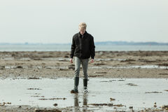 Boy walking through large puddle near beach Royalty Free Stock Photography
