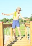 Boy walking on moving bridge stock photo