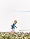 Boy walking near ocean at beach Royalty Free Stock Photo