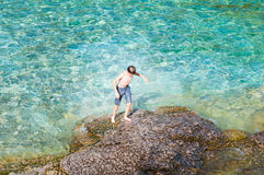 Boy walking out of a beautiful lake after a swim Stock Image