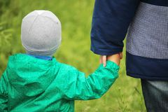 A little boy holding his mom`s hand. A boy walking oute holding his mother hand royalty free stock photos