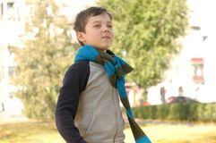 Boy walking in the park on a joyful sense of freedom. A long scarf is tied around the boy`s neck Stock Images