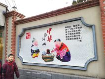 Boy walking past propaganda poster on Shanghai street. A photograph showing a young child wearing the red neck scarf, walking past a big colorful poster of the royalty free stock image
