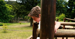 Boy walking on a playground ride in park stock footage