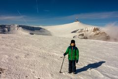 Boy with walking pole on a mountain path in winter stock image