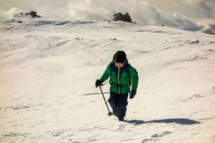 Boy with walking poles on a path in the mountains royalty free stock photography