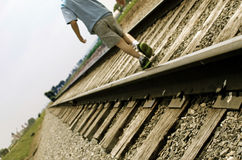 Boy walking on railroad track Stock Photos