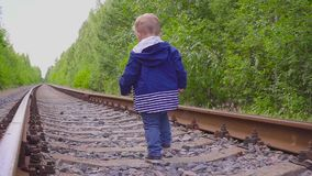Boy walking on the railway. Dangerous games and entertainment. Summer day. Boy walking on the railway. Dangerous games and entertainment. Summer day hd stock video