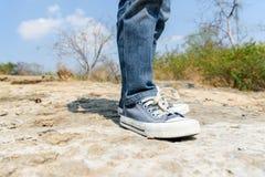 Boy walking on the rocky land. Royalty Free Stock Image