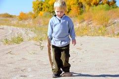 Boy walking on sand Stock Photos