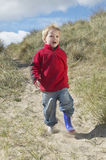 Boy Walking On Sand At Beach Stock Photos