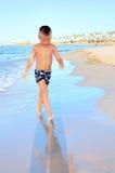Boy walking on sandy beach Stock Photos