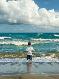 Boy walking in the sea Royalty Free Stock Images