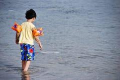 Boy walking in the sea Stock Image