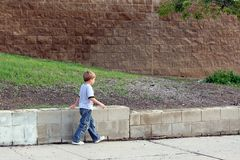 Boy walking on sidewalk Stock Photos