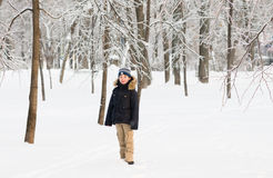 Boy walking in a snowy park on a sunny day Stock Photo