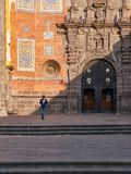Boy walking in square of baroque convent stock photography