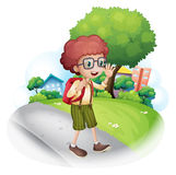 A boy walking at the street carrying a backpack Stock Images