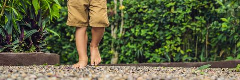 Boy Walking On A Textured Cobble Pavement, Reflexology. Pebble stones on the pavement for foot reflexology BANNER long format royalty free stock photography