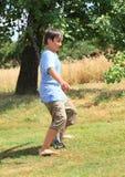 Boy walking thru sprinkler Stock Images