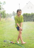 Boy walking thru sprinkler Stock Photography