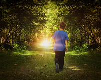 Boy Walking to Birght Light in Woods Royalty Free Stock Photos