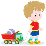 Boy walking with toys Stock Photos