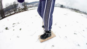 Boy walking with two wooden pads attached to his shoes stock footage