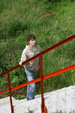 Boy walking up stairs outdoors Stock Image