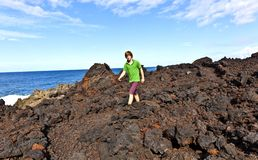 Boy walking in volcanic area Stock Photography