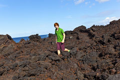 Boy walking in volcanic area Stock Image