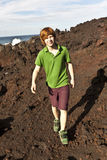 Boy walking in volcanic area Stock Images