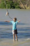 Boy walking on water. A young boy is swinging on a rope on the river looks like he is walking on water Stock Photography